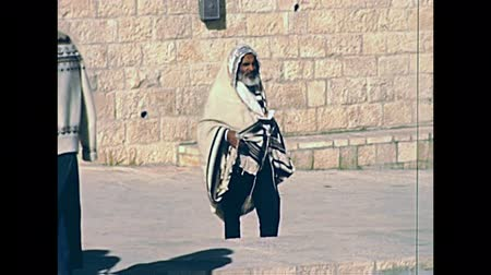 tallit : JERUSALEM, ISRAEL - CIRCA 1981: Jewish people and tourists in typical old fashion clothing and talled shawl, walking in Old City of Jerusalem, Western Wall square. Historic footage on 1980s in Israel.
