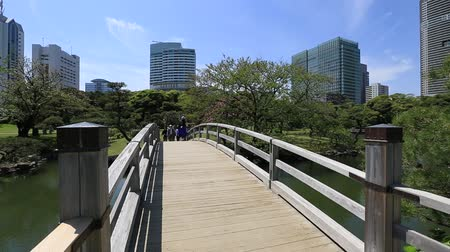 chuo city : Tokyo, Japan -April 20, 2017:Wooden path in Hamarikyu Gardens with buildings of Shiodome-Shimbashi District background. Hama Rikyu is a large beautiful landscape garden in Chuo district, Sumida River