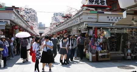 kaminarimon : Tokyo, Japan - April 19, 2017: crowd of people in spring sakura on Nakamise-dori, street with food and souvenirs shops, connetting the Kaminarimon Gate at the entrance of Senso-ji Buddhist Temple.