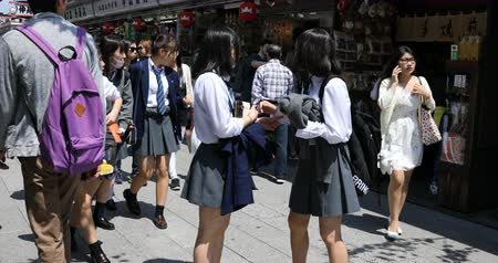 kaminarimon : Tokyo, Japan - April 19, 2017: young teens in school uniforms walking on Nakamise Dori, street with food and souvenirs shops, eating an ice cream. Kaminarimon Gate of Sensoji Temple on background.