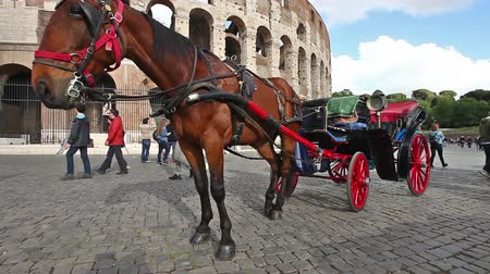 flavium : Rome, Italy - May 12, 2016: Typical horses carriages with tourists in front of Colosseo, Colosseum, Flavian Amphitheatre, the largest amphitheater in the world and one of the symbols of Italy.