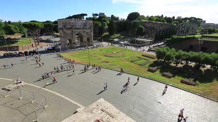 costantino : Rome, Italy - May 12, 2016: 180 degrees panoramic aerial view of Colosseum square with tourists walking beside the Arch of Constantine at sunset, between the roman forum the Roman road.