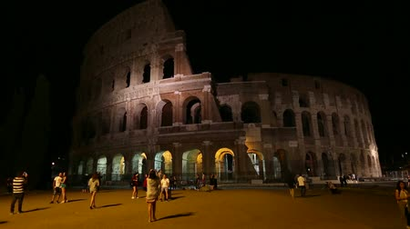 flavium : Rome, Italy - May 12, 2016: Rome coliseum by night with tourists visiting, Flavian Amphitheatre, the largest amphitheater in the world and one of the symbols of Italy and Rome.