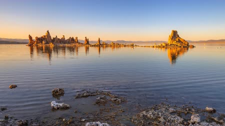 wapń : calcareous tufa formation reflects on the smooth waters of Mono Lake, one of oldest lakes in North America. Mono Lake Tufa State Natural Reserve, California, United States. Sunset time lapse.