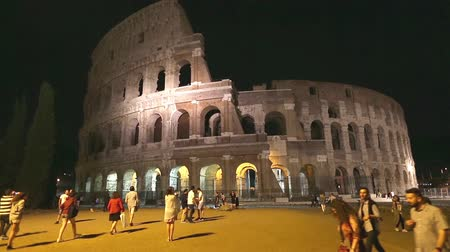 flavium : Rome, Italy - May 12, 2016: Rome colosseo by night with tourists visiting, Flavian Amphitheatre, the largest amphitheater in the world and one of the symbols of Italy and Rome. timelapse Stock Footage