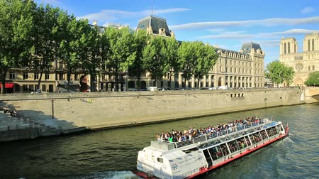 neuf : PARIS, FRANCE - JULY 2, 2017: Tourist cruise on Seine river. Bateau-mouche from Pont Neuf bridge and Notre Dame church on background. Tourist traveler and popular landmarks of Paris.