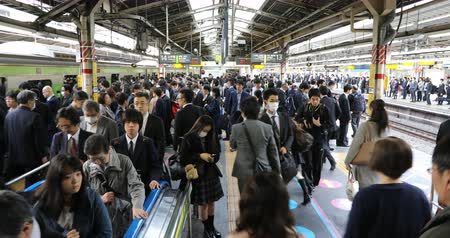chuo city : Tokyo, Japan - April 17, 2017: commuters on the sidewalk waiting for the train at rush hour in Shinjuku Station, Tokyos main station. Yamanote Line (loop) and Sobu Line local signboard.
