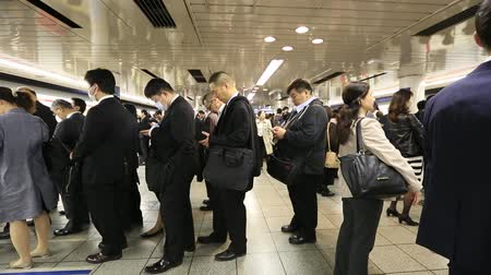 řádek : Tokyo, Japan - April 17, 2017: rush hour crowd of people in queue at Marunouchi Line, subway line in Tokyo at Shinjuku Station. On maps and signboards, the line is shown in red and with the letter M.