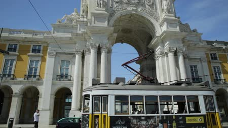 augusta : Lisbon, Portugal - August 25, 2017: historic yellow Tram 25 in front of Rua Augusta Triumphal Arch in Commerce Square or Praca do Comercio.