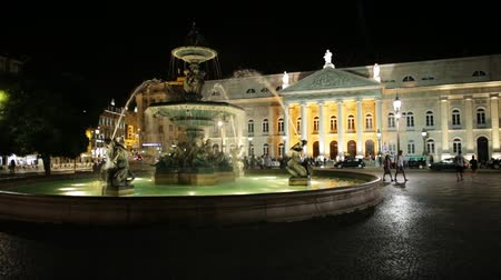 d day : Lisbon, Portugal - August 26, 2017: baroque fountain on popular Praca Dom Pedro IV or Rossio Square in Lisbon downtown, Portugal. National Theater D. Maria on background by night.