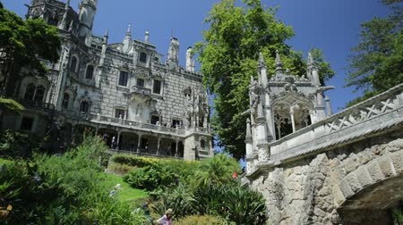 regaleira : SINTRA, PORTUGAL - AUGUST 9, 2017: Gothic facade of grand house with ornamental bridge of Regaleira Palace, in Portuguese Quinta da Regaleira, and its gardens, famous landmark and Unesco Heritage.