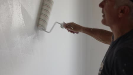 pincel : Painter with paint roller and bucket in empty white room for dyeing in white the wall in slow motion. copy space.