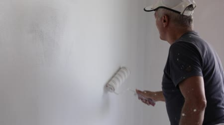 decorador : slow motion of paint roller in empty white room with whitewasher. copy space. Stock Footage