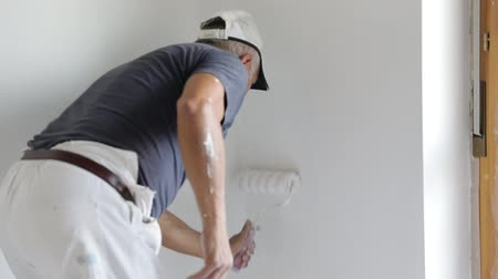 decorador : Painter man painting a blank wall, with paint stick roller in empty white room with copy space. Vertical Shot.