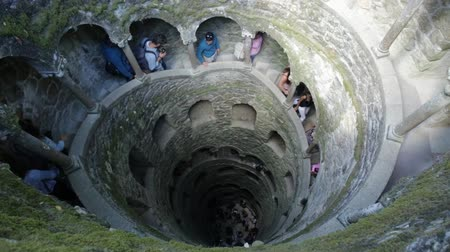 monteiro : SINTRA, PORTUGAL - AUGUST 9, 2017: people in the spiral staircase. tourists enjoying in Quinta da Regaleira, Sintra, Portugal. Details of Initiation well. Architecture background, aerial view.