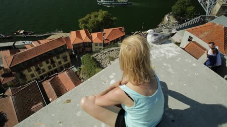 vila : Carefree woman with seagull looking picturesque Porto and Ribeira district skyline. Aerial view of Dom Luis I Bridge on Douro River, Vila Nova de Gaia, Portugal. Female tourist enjoying in sunny day