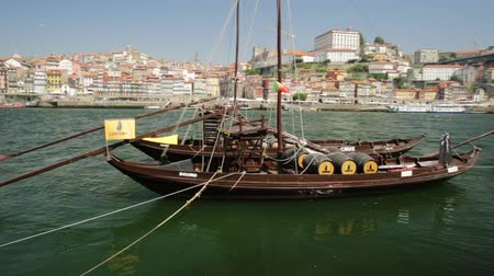 vila : Porto, Portugal - August 13, 2017: Picturesque old Oporto waterfront with Ribeira skyline. A traditional rabelo boats on Douro River with Dom Luis I Bridge from Vila Nova de Gaia, Porto. Sunny day.