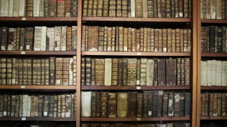 portugese : Coimbra, Portugal - August 14, 2017: wooden shelf with historic, decorated, vintage books at University of Coimbra, Europes oldest university. Background of books. Stock Footage