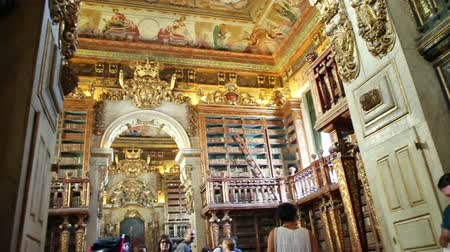 portugese : Coimbra, Portugal - August 14, 2017: interior of the library of Coimbra University with tourists. Unesco World Heritage Site and most important tourist attraction in Upper Coimbra.