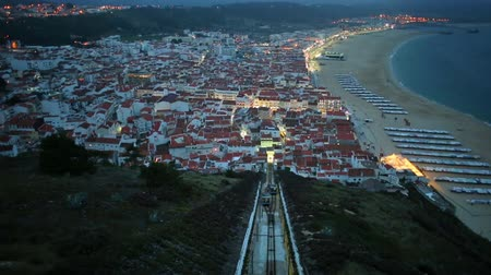 miradouro : Time lapse panorama of Nazare in Portugal by night, the most popular seaside resorts in Silver Coast. Aerial view of skyline, beach and Ascensor da Nazare or Nazare Funicular from Nazare Sitio