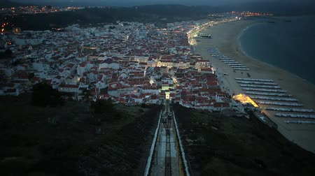 prospective : Nazare, Portugal by evening, the most popular seaside resorts in Silver Coast. Prospective view of popular Ascensor da Nazare or Nazare Funicular from Nazare Sitio, the upper part of city. slow motion Stock Footage