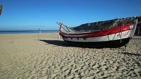 portugese : Nazare, Portugal - August 16, 2017: prospective view of colorful traditional old wooden fishing boats on the beach of fishing village of Nazare. Stock Footage