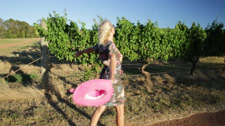 маргарита : Beautiful blonde carefree woman with hat walks near the vineyards. Happy woman enjoying during a popular wine tasting tour in the wine region of Margaret River, Western Australia.