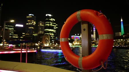 lifebelt : Red life preserver on foreground on walkway of Elizabeth Quay Marina in Perth Downtown, Western Australia. Esplanade and construction cranes on blurred background. Perth capital city by night.