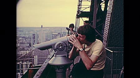 seventy : PARIS, FRANCE - CIRCA 1976: Tourists in vintage 70s dress, looking the panorama of Paris from Eiffel Tower with the telescope. Historic archival footage in Paris city of France in 1970s.