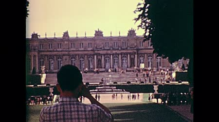 seventy : PARIS, FRANCE - CIRCA 1976: Tourists looking the Palace of Versailles from the Versailles garden. Historic archival footage in Paris city of France in 1970s.