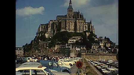 seventy : Mont Saint-Michel, FRANCE - July 12,1976: ground panorama with tourists in the car parking of Historic Saint Michaels Mount in the 70s. People in vintage 1970s dress and vintage cars and bus. Stock Footage