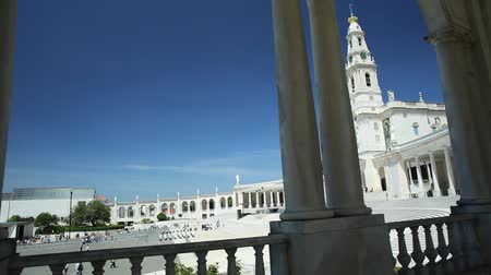 oszlopsor : Fatima, Portugal - August 15, 2017: Sanctuary of Our Lady of Fatima, one of most important Marian Shrines and pilgrimage locations for Catholics. Basilica of Nossa Senhora through the colonnade. Stock mozgókép