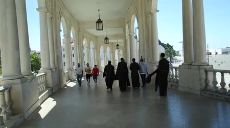 marian : Fatima, Portugal - August 15, 2017: group of nuns walks under arcade at Sanctuary of Our Lady of Fatima, one of the most important Marian Shrines and pilgrimage locations for Catholics. Stock Footage
