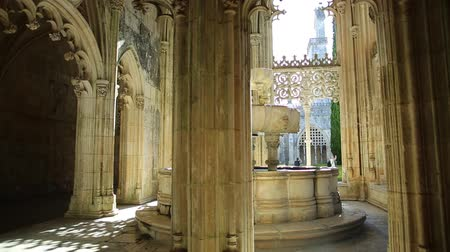 lavatório : Batalha, Portugal - August 16, 2017: glow that filters through the arches surrounding the lavatory or famous fountain of Mateus Fernandes at Monastery of Batalha, Unesco Heritage in Portugal. Stock Footage