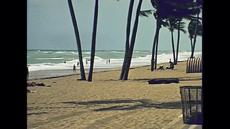 beach panorama : Panorama of the Miami Beach in Florida and its tropical sea, the long white beaches and popular seafront street in 70s with few tourists and buildings. Historical United States of America in 1978. Stock Footage