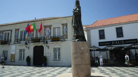 eu : Cascais, Portugal - August 6, 2017: King Peter I Statues in Outubro Square, historic Cascais center, the most popular holiday destination on Lisbon coast.Typical Portuguese mosaic flooring. Blue sky. Vídeos
