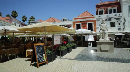portugese : Cascais, Portugal - August 6, 2017: Monument of Portuguese poet Luis De Camoes on Largo Luis de Camoes with cafes and restaurants in Cascais center. People enjoying summer vacations.