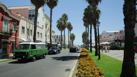portugese : Cascais, Portugal - August 6, 2017: street view of tree-lined boulevard leading to fishing harbor, waterfront and beaches of famous tourist resort of Cascais.Picturesque city of Lisbon Coast in summer