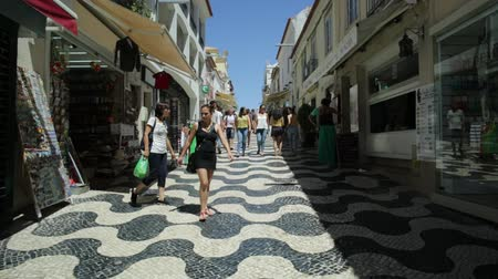 lizbona : Cascais, Portugal - August 6, 2017: POV tourists walking through the historic center streets of Cascais by shopping on a sunny summer day. Cascais is the most famous holiday resort town near Lisbon. Wideo