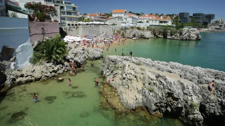 lizbona : Cascais, Portugal - August 6, 2017: Praia da Rainha beach with cliffs in Cascais center, Portugal. Aerial view of Lisbon Coast. People sunbathing and swimming in turquoise sea during summer holidays. Wideo