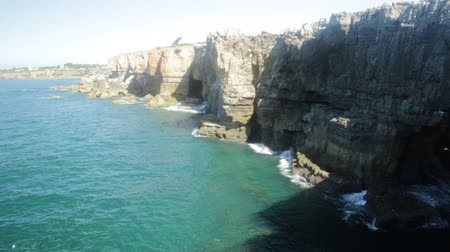 ад : Scenic landscape of Boca do Inferno an open cavern in the coast of Cascais, Portugal. Hells Mouth is a rough cliff formation with a natural arch and touristic sightseeing spot on Atlantic Coast.