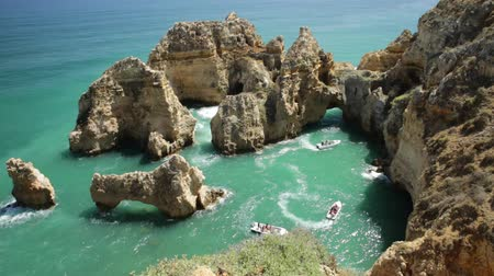 boat tour : Aerial view of scenic landscape of boat trip between cliffs and natural rock formations of Ponta da Piedade in Lagos, Algarve, Portugal. Summer holidays. Tour tourism in Atlantic Ocean. Sunny day.