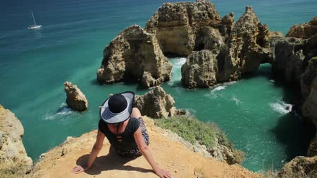 ponta da piedade : Tourism in Algarve. Summer holidays in Portugal, Europe. Lifestyle tourist sitting on promontory of Ponta da Piedade. Caucasian woman looking amazing views of iconic cliffs of turquoise sea of Lagos.