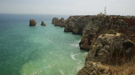 oszlopsor : Spectacular Algarve coast with Ponta da Piedade lighthouse in the distance. Lagos, Algarve in Portugal. Tour tourism in Atlantic Ocean. Aerial view of rock formation and pillars of Lagos bay.