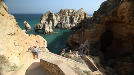 ponta da piedade : Lagos, Portugal - August 22, 2017:Time lapse of tourists on the steps leading down to the caves at Ponta da Piedade in Lagos, one of the main tourist destinations in Algarve Coast, Portugal.Sunny day. Stock Footage