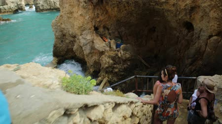 ponta da piedade : Lagos, Portugal - August 22, 2017:POV of tourists on stairs awaiting boat trip for caves, arches and rock formations of Ponta da Piedade in Lagos, one of the main tourist destinations in Algarve Coast