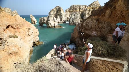 ponta da piedade : Lagos, Portugal - August 22, 2017: Timelapse of tourists on steps taking pictures and selfies of the caves at Ponta da Piedade in Lagos, one of the main tourist destinations in Algarve Coast, Portugal