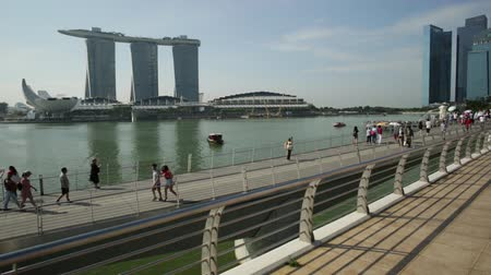 skypark : Singapore - April 28, 2018: people walking on Jubilee Bridge. ArtScience Museum, Marina Bay Sands Casino, Merlion Statue and Financial District skyscrapers from Esplanade Bridge. Sunny day blue sky.