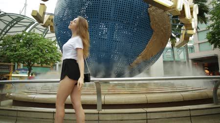 bull ring : Singapore - May 2, 2018: Universal Studios globe in Sentosa island and tourist girl posing for taking pictures in turn. Universal Studios Singapore is Southeast Asias first Hollywood movie theme park Stock Footage