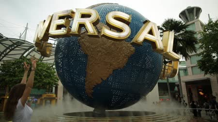 bull ring : Singapore - May 2, 2018: tourist women visiting the Hollywood movie theme park in Sentosa island and posing with Universal Studios world globe in sunset light for selfie pictures. Stock Footage
